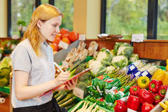 Woman in supermarket making apprenticeship. Woman in supermarket with clipboard making apprenticeship to become salesperson stock photo