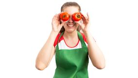 Woman supermarket or retail employee covering eyes with tomatoes royalty free stock photography