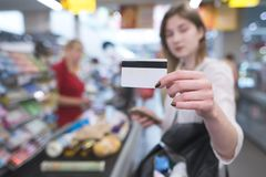 Woman is at the supermarket`s cash desk and shows a card in the camera. Payment by credit card. At a supermarket. Card in the hands of a woman close-up on the stock images