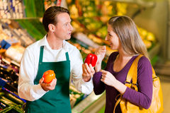 Woman in supermarket and shop assistant royalty free stock photo