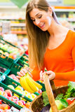 Woman in supermarket shopping groceries Stock Photos