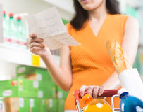 Woman at supermarket with shopping list Stock Photos