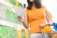 Woman at supermarket with shopping list Royalty Free Stock Photography