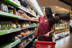 Woman at supermarket. Smiling woman doing shopping in supermarket and deciding what to buy. Happy woman shopping in a grocery store and holding shopping basket Royalty Free Stock Image