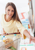 Woman at the supermarket. Smiling young woman doing grocery shopping at the supermarket, she is taking products from a shelf Stock Photography