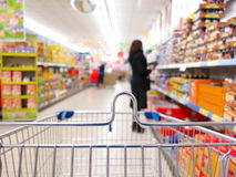 Woman at the supermarket with trolley. Woman shopping at the supermarket with trolley Stock Image