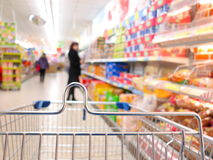 Woman at the supermarket with trolley. Woman shopping at the supermarket with trolley Royalty Free Stock Photo