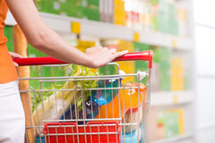Woman at supermarket with trolley. Woman shopping at supermarket, hands on trolley close-up Royalty Free Stock Photography