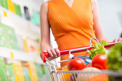 Woman at supermarket with trolley Stock Images