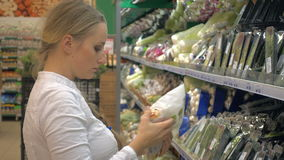 Woman in a supermarket at the vegetable shelf shopping stock video