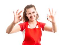 Woman supermarket worker making ok gesture. Young woman supermarket worker making ok gesture with hands and smiling as happy retail worker concept isolated on stock image