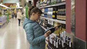 Woman in supermarket. Young caucasian woman in blue jacket choosing sparkling wine on store shelves background. stock video