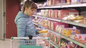 Woman in supermarket. Young caucasian woman in blue jacket reading label of cheese putting it in the cart. stock footage