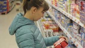 Woman in supermarket. Young caucasian woman in blue jacket reading yogurt label. stock video