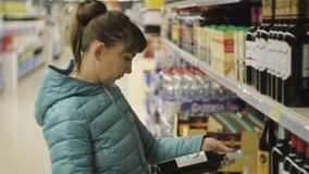 Woman in supermarket. Young caucasian woman in blue jacket reading the label on the dark bottle choosing red wine. stock footage