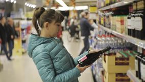 Woman in supermarket. Young caucasian woman in blue jacket reading the label on the dark bottle choosing sparkling wine. stock video footage
