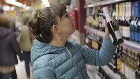 Woman in supermarket. Young caucasian woman in blue jacket reads the label on the small bottle choosing sparkling wine. stock video