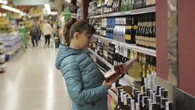 Woman in supermarket. Young caucasian woman in blue jacket takes a bottle from the shelf choosing sparkling wine. stock video