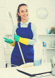Woman with supplies cleaning in office Royalty Free Stock Photo