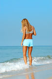Woman in surf on beach Royalty Free Stock Images