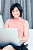 Woman surf at home. Pretty young woman with headphones and laptop on white sofa at home Stock Image
