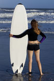 Woman with Surfboard looking at Ocean Stock Photos
