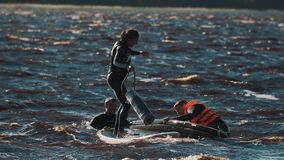 Woman on a surfboard trying to find balance , but falls into the water stock video footage
