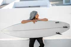 Woman with surfboard on the white city background Stock Photo