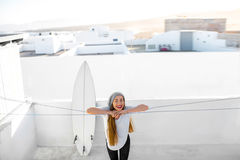 Woman with surfboard on the white city background Stock Photos