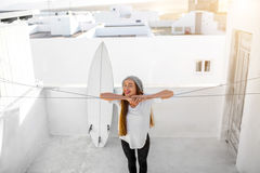 Woman with surfboard on the white city background Royalty Free Stock Images