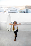 Woman with surfboard on the white city background Royalty Free Stock Image