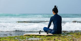 Woman surfer sit on reef stock images