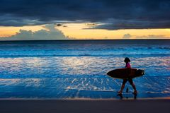 Woman surfer at sunset. Bali Royalty Free Stock Image