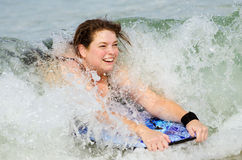 Woman surfing on bodyboard at beach Royalty Free Stock Images