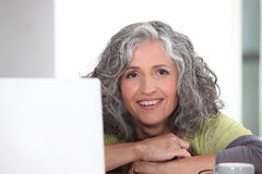 Woman surfing the internet. Grey-haired woman surfing the internet Royalty Free Stock Images