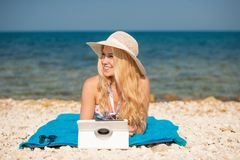 Woman surfing internet looking at tablet on the beach.  stock images