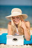 Woman surfing internet looking at tablet on the beach Stock Photo
