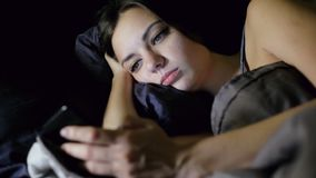 Woman surfing internet while lying in bed in the bedroom at night, looks photo, chating. Woman surfing internet while lying in bed in the bedroom at night stock footage