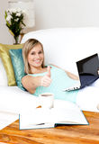 Woman surfing the internet lying on a sofa. Charming woman surfing the internet lying on a sofa at home Royalty Free Stock Photography