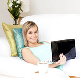 Woman surfing the internet lying on a sofa Stock Photos