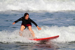 Woman surfing in Kuta Beach Royalty Free Stock Images