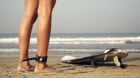 A woman is surfing. A surfer girl on the beach puts a leash on her leg