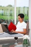 Woman surfing web. Young Indian Asian woman relaxes using the internet at home Stock Image