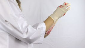Woman surgeon doctor in white robe take off bloody gloves hands Stock Images