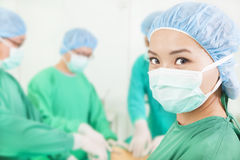 Woman surgeon working with team in a surgical room Royalty Free Stock Image