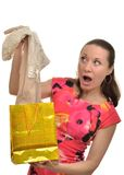 Woman with surprise examines new clothes obtained as a gift Royalty Free Stock Images