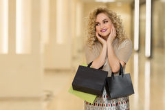 Woman surprise holds cheeks by hand .Beautiful girl with shopping bags pointing to looking left. Presenting your product. Stock Image