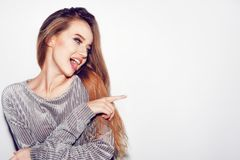 Woman surprise showing product .Beautiful girl with long hair pointing to the side . Make-up. Expressive facial expressions. Presenting your product. on white royalty free stock photos