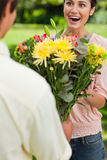 Woman surprised as she is presented with flowers by her friend Royalty Free Stock Images