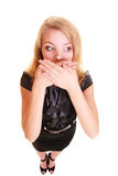 Woman surprised buisnesswoman covers her mouth isolated. Surprised woman shocked buisnesswoman in black dress covers mouth with hand isolated on white Royalty Free Stock Images